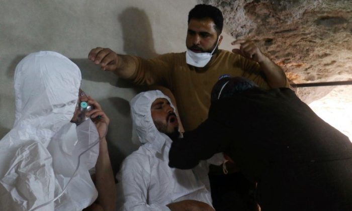 A man breathes through an oxygen mask as another one receives treatments, after what rescue workers described as a suspected gas attack in the town of Khan Sheikhoun in rebel-held Idlib, Syria April 4, 2017. (REUTERS/Ammar Abdullah/File Photo)