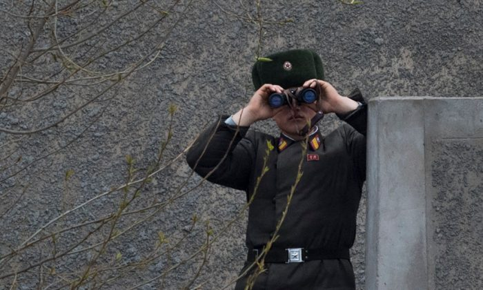 A North Korean soldier uses his binoculars to look across the Yalu river near Sinuiju, opposite the Chinese border city of Dandong on April 14, 2017. (JOHANNES EISELE/AFP/Getty Images)
