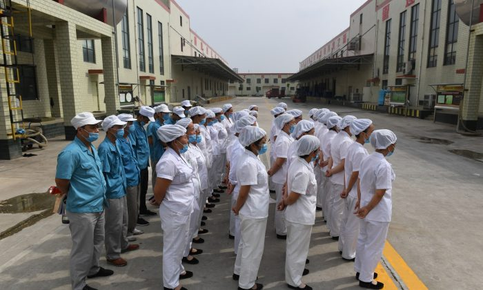 Workers lined up to sing communist 'red' songs at an instant noodle factory, near a village in China's central Henan Province on Sept. 29, 2017. Recently the Chinese Communist Party has further extended its control on companies with both private and foreign-owned, with party branches. (Greg Baker/AFP/Getty Images)