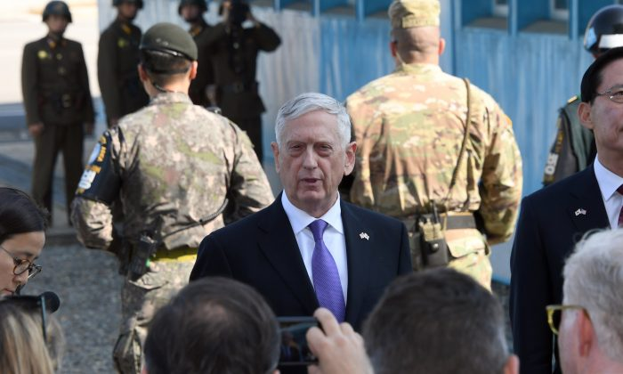 Secretary of Defence Jim Mattis (C) speaks to the media as South Korean Defence Minister Song Young-Moo (R) looks on during a visit to the Demilitarized Zone. North Korean soldiers can be seen in the background. (JUNG YEON-JE/AFP/Getty Images)