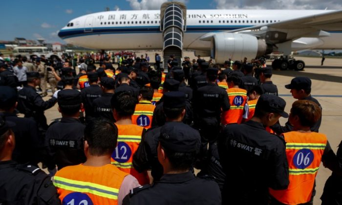Chinese nationals (in orange vests) who were arrested over a suspected internet scam, are escorted by Chinese police officers before they were deported at Phnom Penh International Airport, in Phnom Penh, Cambodia, October 12, 2017. (Reuters/Samrang Pring)