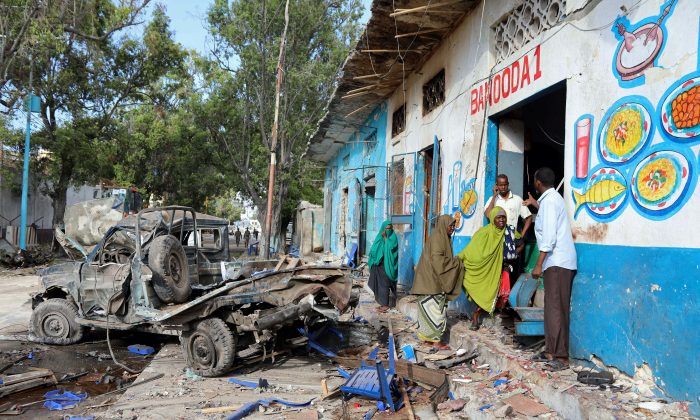 Residents gather at the scene of a suicide car bomb explosion, at the gate of Naso Hablod Two Hotel in Hamarweyne district of Mogadishu, Somalia Oct. 29, 2017. (REUTERS/Feisal Omar)