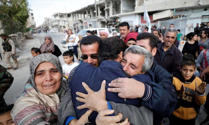 Relatives hug one of the hostages held by ISIS terrorists who escaped from his captors in Qaryatayn town in Homs province, Syria Oct. 29, 2017. (REUTERS/Omar Sanadiki)