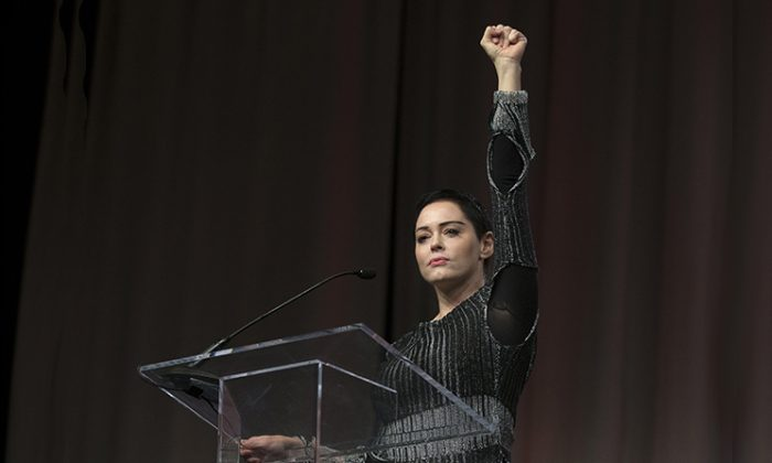 Actress Rose McGowan raises her fist during her opening remarks to the audience at the Women's March / Women's Convention in Detroit, Michigan, on October 27, 2017. (Rena Laverty/AFP/Getty Images)