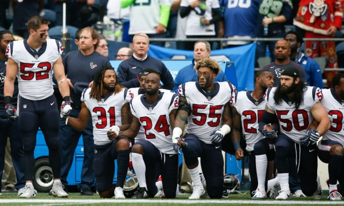 Members of the Houston Texans stand and kneel before the game against the Seattle Seahawks at CenturyLink Field in Seattle, Washington, on Oct. 29, 2017. During a meeting of NFL owners earlier in October, Houston Texans owner Bob McNair said 'we can't have the inmates running the prison', referring to player demonstrations during the national anthem. (Otto Greule Jr/Getty Images)
