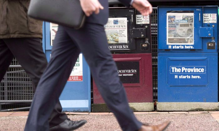 """Pedestrians pass newspaper boxes in downtown Vancouver. The """"narrowing of the window of public opinion"""" in today's media is a dangerous thing, says author and historian Gerry Bowler. (The Canadian Press/Jonathan Hayward)"""