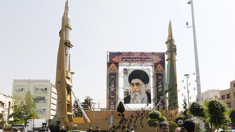 Iranians walk past Sejjil (L) and Qadr-H medium range ballistic missiles displayed next to a portrait of Iranian Supreme Leader Ayatollah Ali Khamenei on the occasion of the anniversary of the 1980s Iran-Iraq war, on September 25, 2017, on Baharestan square in Tehran. (Atta Kenare/AFP/Getty Images)