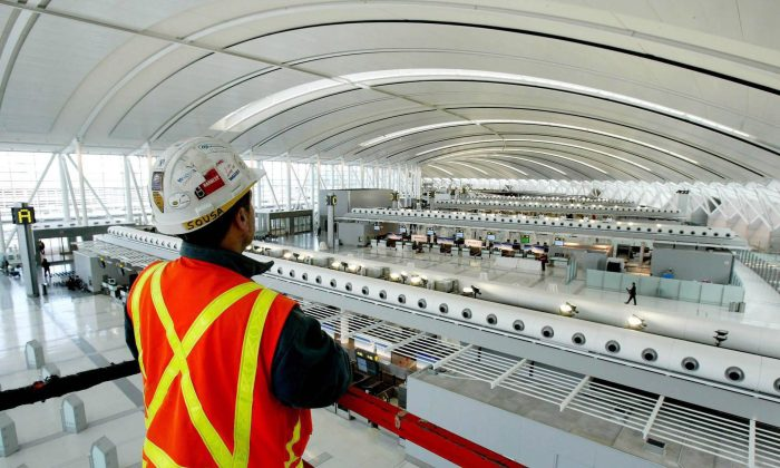 An Aecon employee looks at Toronto Pearson International Airport's check-in area. A Chinese state-owned enterprise is looking to acquire the Canadian construction firm, necessitating a government review. (Canadian Press/AP, Tobin Grimshaw)