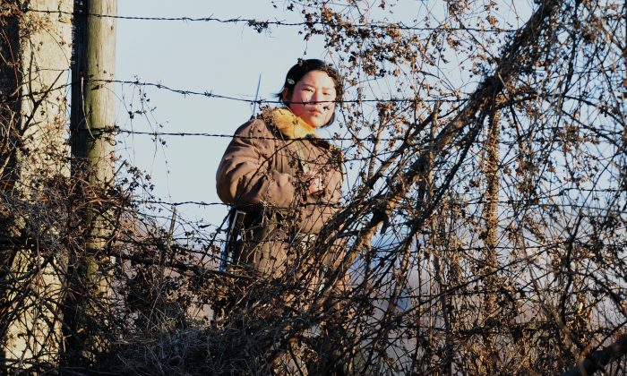 An armed North Korean female soldier keeps watch behind a barbed wire fence on the banks of the Yalu River near Dandong in northeast China's Liaoning province on Nov. 25, 2010. (FREDERIC J. BROWN/AFP/Getty Images)