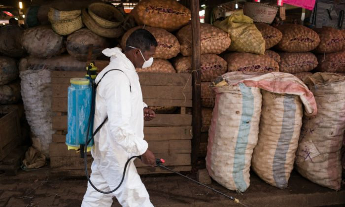 A council worker walks past sacks of potatoes as he sprays disinfectant during the cleanup of the market of Anosibe in the Anosibe district, one of the most unsalubrious district of Antananarivo on Oct. 10, 2017. (Rijasolo/AFP/Getty Images)