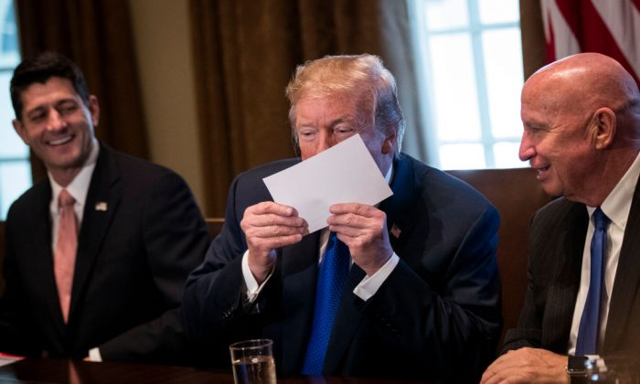 Flanked by Speaker of the House Paul Ryan and House Ways and Means Committee chairman Rep. Kevin Brady (R-TX), President Donald Trump kisses an example of what a new tax form may look like as he speaks about tax reform legislation in the Cabinet Room at the White House in Washington, DC, on Nov. 2, 2017. (Drew Angerer/Getty Images)