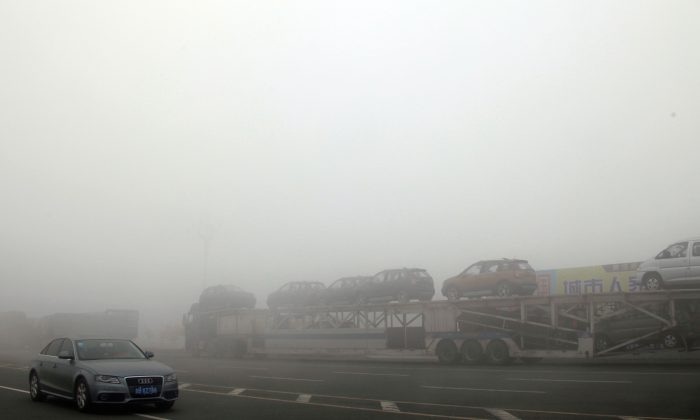 Cars wait on a highway due to heavy smog in Jilin Province, China, on Oct. 22, 2013. (STR/AFP/Getty Images)