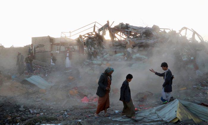 People walk at the site of an air strike in the northwestern city of Saada, Yemen on Nov. 1, 2017. (REUTERS/Naif Rahma)
