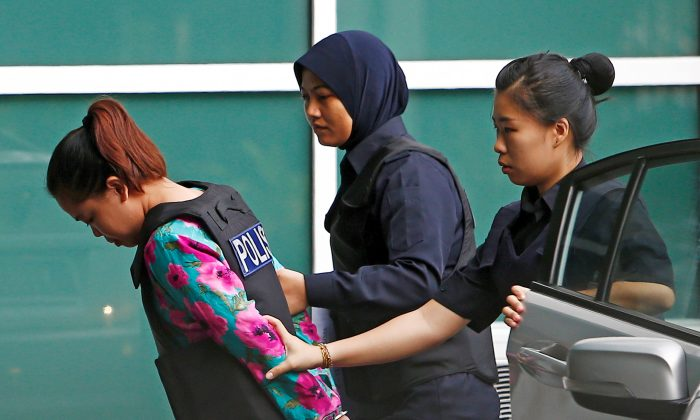 Indonesian Siti Aisyah who is on trial for the killing of Kim Jong Nam, the estranged half-brother of North Korea's leader, is escorted as she arrives at the Department of Chemistry in Petaling Jaya, near Kuala Lumpur, Malaysia on Oct. 9, 2017. (REUTERS/Lai Seng Sin)
