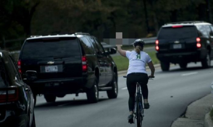 A woman on a bike gestures with her middle finger as a motorcade with US President Donald Trump departs Trump National Golf Course in Sterling, Virginia on Oct. 28, 2017. (BRENDAN SMIALOWSKI/AFP/Getty Images)