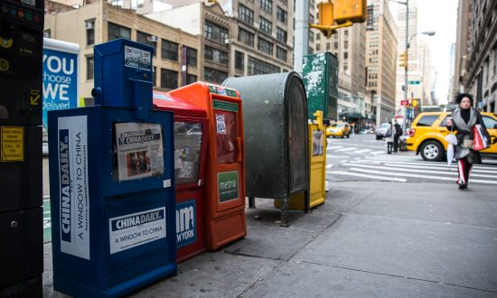 A paid China Daily newspaper box next to free daily papers in Midtown Manhattan, New York, on Dec. 6, 2017. (Benjamin Chasteen/The Epoch Times)