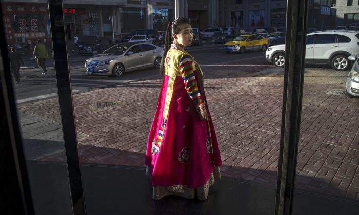 A North Korean restaurant worker tries to attract customers in the border city of Dandong, Liaoning province, northern China across the Yalu River from the border city of Sinuiju, North Korea on May 23, 2017 in Dandong, China. Reports from inside China reveal North Korean workers are being forced out of the country. (Kevin Frayer/Getty Images)