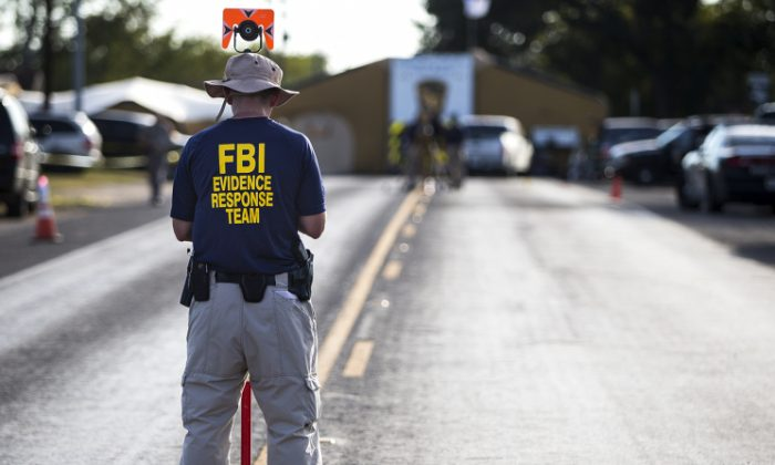 A member of the FBI's Evidence Response Team works on the crime scene of the mass shooting at the First Baptist Church in Sutherland Springs, Texas, on Monday, Nov. 6, 2017. (Nick Wagner/Austin American-Statesman via AP)