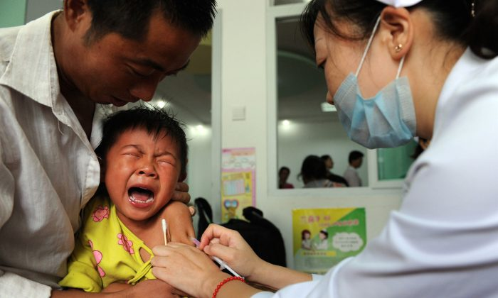 A Chinese boy screams out in pain as he gets inoculated against measles in Hefei City, in eastern China's Anhui Province on September 11, 2010. (STR/AFP/Getty Images)