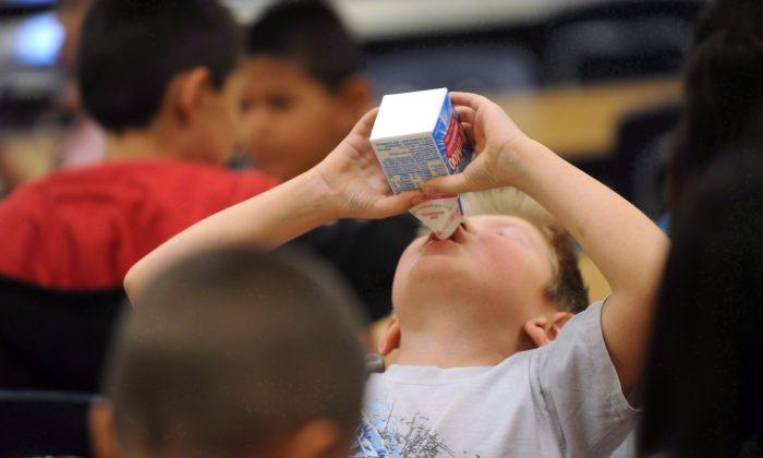 A child drinks milk during lunch at a school in Abilene, Texas. Experts are warning against relying on plant-based drinks as the main beverage for babies and young kids.  (The Canadian Press/AP/Nellie Doneva)