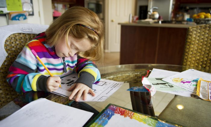 A young girl does her homework in her dining room in Centreville, Md., after class at Centreville Elementary on April 30, 2013. (Jim Watson/AFP/Getty Images)