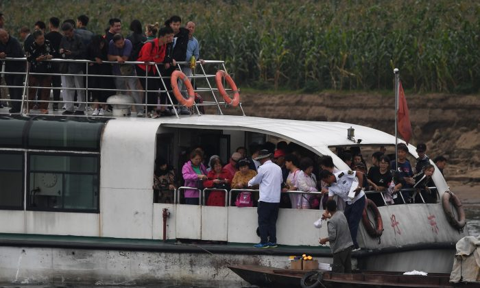 A North Korean man (bottom R) sells items to Chinese tourists on the Yalu river near the North Korean town of Sinuiju, opposite the Chinese border city of Dandong in Liaoning Province on September 5, 2017. (Greg Baker/AFP/Getty Images)
