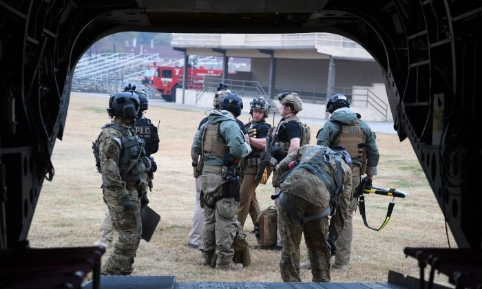 Secret Service counter-assault team members, accompanying U.S. President Donald Trump in another helicopter, prepare to board a helicopter as they attempt to fly to the Demilitarized Zone (DMZ) over Seoul on Nov. 8, 2017. The crew was forced to turn around before landing due to bad weather. (JIM WATSON/AFP/Getty Images)