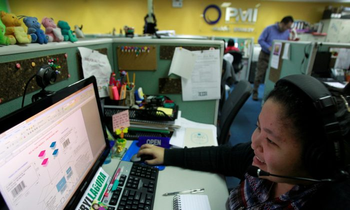 A call center agent talks to a client in the U.S. as she works the overnight shift in Manila's Makati financial district Feb. 6, 2012. (REUTERS/Erik De Castro/File Photo)