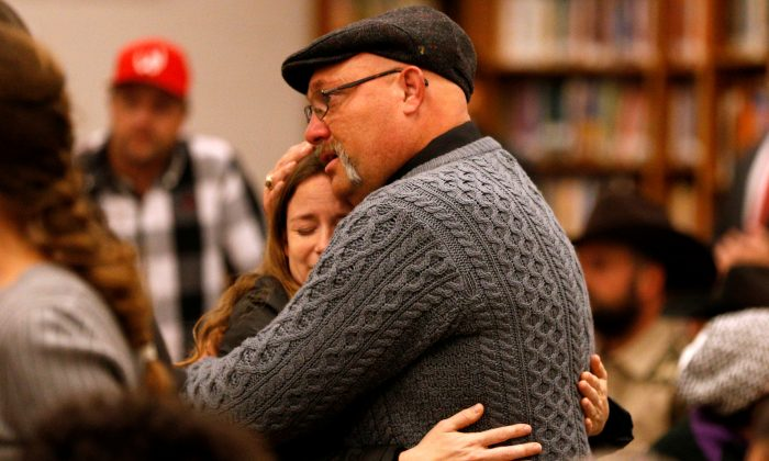 Pastor Frank Pomeroy hugs a woman during a visit with family and victims of the shooting. (REUTERS/Jonathan Bachman)