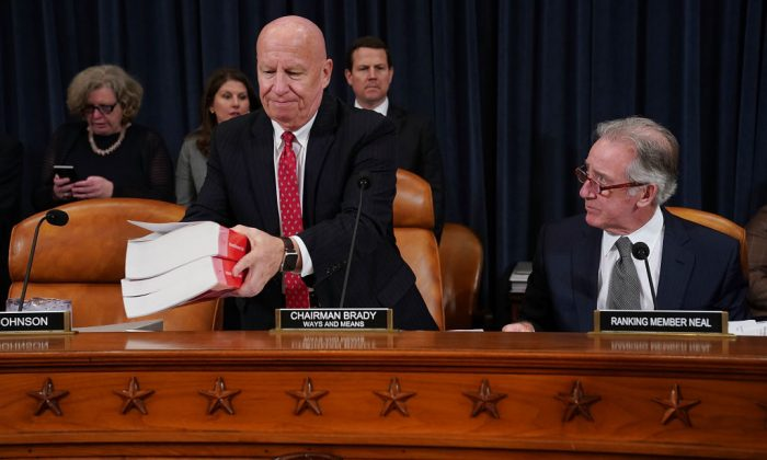 House Ways and Means Committee Chairman Kevin Brady (R-TX) (L) sets down a copy of the current tax code as he and ranking member Rep. Richard Neal (D-MA) prepare for the first markup hearing of the proposed GOP tax reform legislation in the Longworth House Office Building on Capitol Hill in Washington, DC, November 6, 2017.  (Chip Somodevilla/Getty Images)