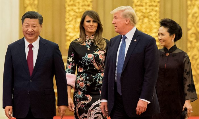 United States President Donald Trump speaks to Chinese leader Xi Jinping, as First Lady Melania Trump and Xi's wife Peng Liyuan look on, at the Great Hall of the People in Beijing on Nov. 9, 2017. (Jim Watson/AFP/Getty Images)