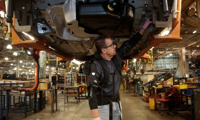 Ford Motor Co assembly worker Paul Collins wears a EksoVest as he works on the assembly line producing the Ford Focus and C-max at Wayne Assembly plant in Wayne, Michigan, U.S., Nov. 9, 2017.  (REUTERS/Rebecca Cook)