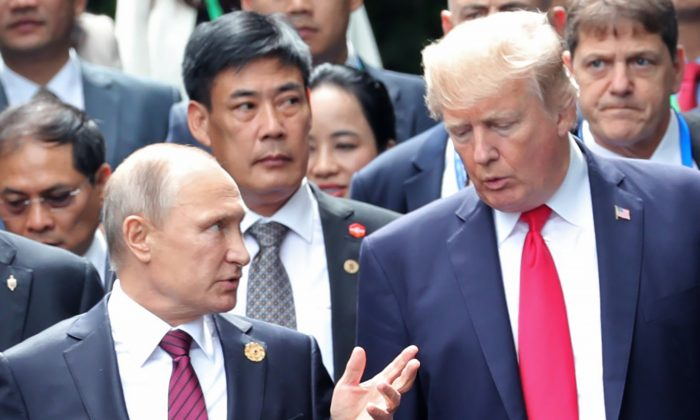 """President Donald Trump and Russia's President Vladimir Putin talk as they make their way to take the """"family photo"""" during the Asia-Pacific Economic Cooperation (APEC) leaders' summit in Danang, Vietnam, on Nov. 11, 2017. (MIKHAIL KLIMENTYEV/AFP/Getty Images)"""