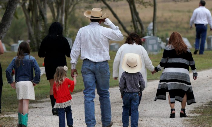A mourner arrives with his children for the burial of Richard and Therese Rodriguez after the husband and wife were killed in the shooting at First Baptist Church of Sutherland Springs in Texas, U.S., Nov. 11, 2017. (REUTERS/Rick Wilking)