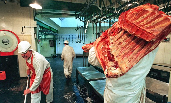 A worker lugs a carcass of beef at Smithfield market in London. The UK government is requiring abattoirs to install CCTV from spring 2018. (Sinead Lynch/AFP/Getty Images)
