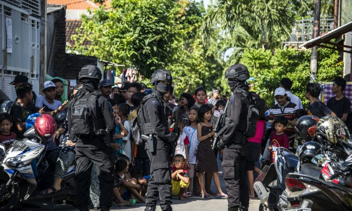 Members of the Densus 88 counter-terrorism police cordon off a road as they search a house in Surabaya, East Java province, on June 19, 2017, following the arrest of a man suspected of links with ISIS. (JUNI KRISWANTO/AFP/Getty Images)