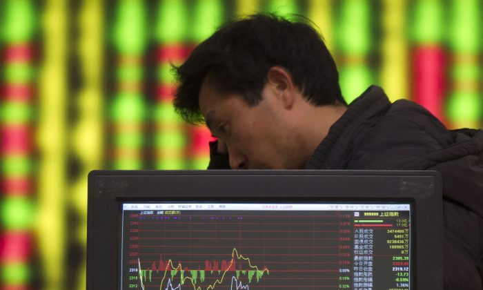 An investor watches the electronic board at a stock exchange hall in Shaoyang City, Hunan Province in China on January 30, 2012. (VCG via Getty Images)