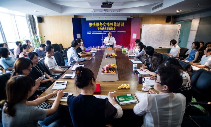 """Shu Xin, the head of Weiqing, a company that offers a team of """"mistress hunters,"""" speaks to his colleagues during a meeting in Shanghai on July 8, 2016. (Johannes Eisele/AFP/Getty Images)"""