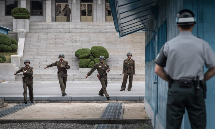 A South Korean soldier (R) stands before North Korean soldiers walking towards the military demarcation line separating North and South Korea at the truce village of Panmunjom on Oct. 12, 2017. A North Korean soldier at Panmunjom defected to the South on Nov. 13, 2017, and was shot and wounded by the North Korean military while crossing the border. (AFP/Getty Images)