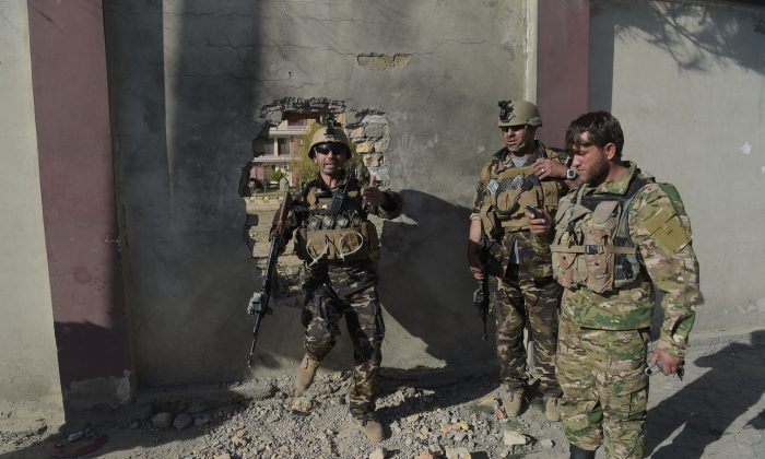 Afghan security personnel leave through a hole of a perimeter wall after gunmen disguised as policemen stormed a television station in Kabul on Nov. 7, 2017. Gunmen disguised as policemen stormed a television station in Kabul on Nov. 7, killing at least two people and wounding several others in the latest deadly attack on Afghan journalists. The assault, claimed by the Islamic State group, lasted about three hours before Afghan special forces overpowered the attackers armed with guns and grenades and freed staff trapped inside the building. (SHAH MARAI/AFP/Getty Images)