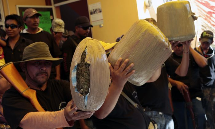 Vigilante group members at the community of Petaquillas show weapons and marijuana allegedly seized during an operation to apprehend suspected offenders, in Chilpancingo, Guerrero State, Mexico, on Feb. 1, 2015. (Pedro PARDO/AFP/Getty Images)