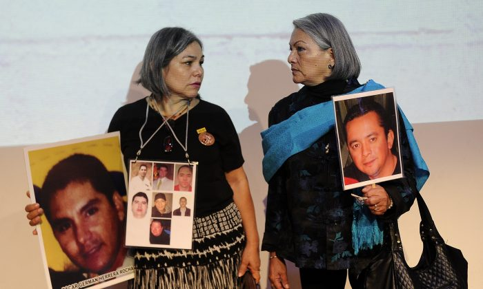 Rosario Villanueva (L) and Yolanda Moran hold pictures of their missing sons Oscar German Herrera and Dan Jeremeel Fernandez, who disappeared in 2009 and 2008 respectively, as they attend the presentation of the independent inquiry into the massacre of 72 migrants in San Fernando, Tamaulipas in Aug. 2010 and the disappearance of residents of Allende, Coahuila, in 2011, at the Museum of Memory and Tolerance in Mexico City on Oct. 9, 2016. (PEDRO PARDO/AFP/Getty Images)