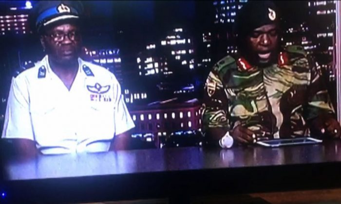 """This screen grab taken early on Nov. 15, 2017 from a television broadcast on the Zimbabwe Broadcasting corporation (ZBC) shows Zimbabwe Major General Sibusiso Moyo (R) reading a statement at the ZBC in Harare. Zimbabwe's military appeared to be in control of the country on Nov. 15 as generals denied staging a coup but used state television to vow to target """"criminals"""" close to President Robert Mugabe.(Dewa Mavhinga/AFP/Getty Images)"""