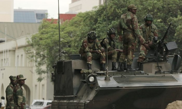 Soldiers are seen next to and on the armoured vehicle on the street in central Harare, Zimbabwe, Nov. 16, 2017. (Reuters/Philimon Bulawayo)