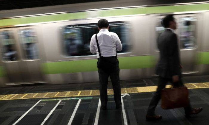 """In this picture taken on Oct. 12, 2017, a man waits for the train at a subway station in Tokyo. The news that a young reporter at Japan's public broadcaster had worked herself to death came as little surprise to those inside the country's media, where a culture of """"fighting spirit"""" has led to excessively long hours. (BEHROUZ MEHRI/AFP/Getty Images)"""