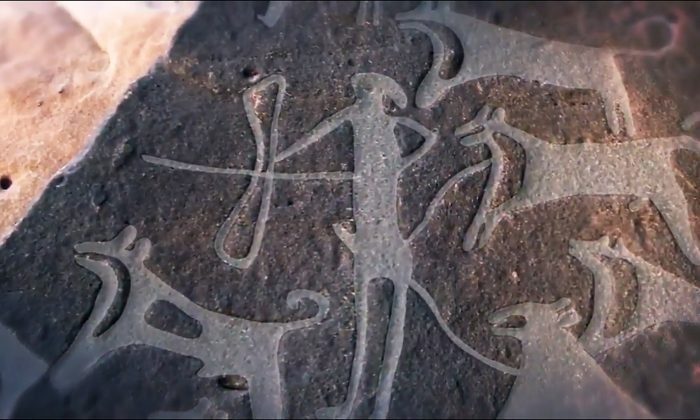 These ancient carvings show human being hunting with domesticated dogs. (YouTube-Science Magazine)