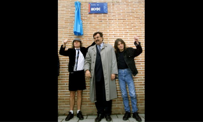 Angus and Malcolm (R) Young, founder members of AC/DC, flank Jose Luis Perez, mayor of the Madrid district of Leganes, following the inauguration of a new street with the group's name, in Leganes, Spain March 22, 2000. (Reuters/Andrew Comas)