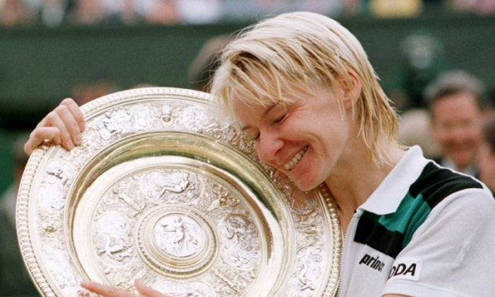 Jana Novotna of the Czech Republic hugs the winner's trophy after victory over Nathalie Tauziat of France in the Women's Singles final at the Wimbledon Tennis Championships July 4, 1998. (Reuters/File Photo)