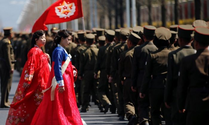 Women wearing traditional clothes walk past North Korean soldiers after an opening ceremony for a newly constructed residential complex in Ryomyong street in Pyongyang, North Korea, on April 13, 2017.  (REUTERS/Damir Sagolj)