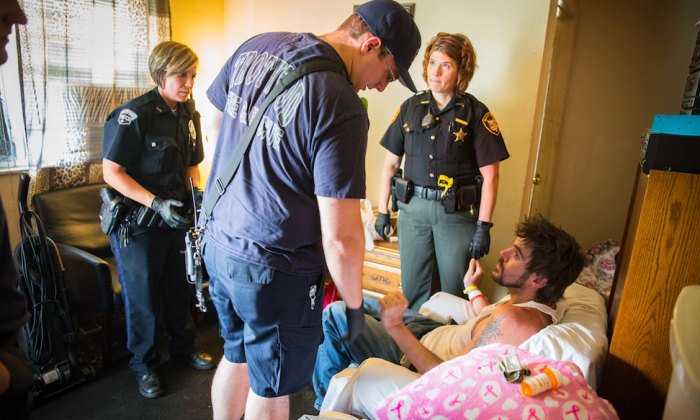 Deputy sheriffs, police officers, and EMS officers at the home of a man who is overdosing in the Drexel neighborhood of Dayton, Ohio, on Aug. 3, 2017. (Benjamin Chasteen/The Epoch Times)